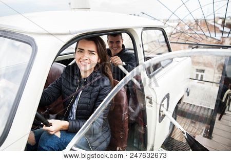 Couple On The Roof Of A House In An Old Car. People