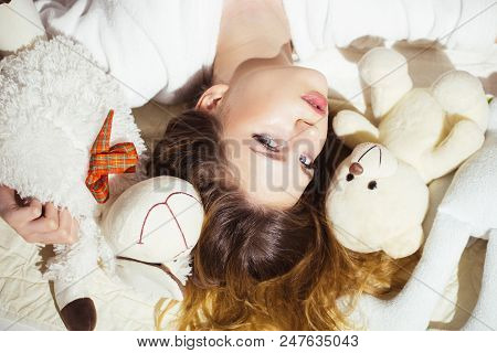 Woman With Long Hair In Tender Pajama Relaxing With Teddy Bear. Girl With Calm Face Lay On Bed. Soft