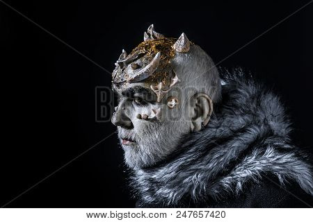Alien, demon, sorcerer makeup. Demon on black background, copy space. Theatrical makeup concept. Senior man with white beard dressed like monster. Man with thorns or warts in fur coat. poster