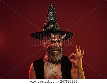 Happy Halloween Man With Devil Horns In Witch Hat Show Ok. Satan Hipster Smile With Beard, Blood, Wo
