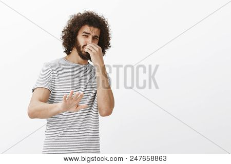You stink, do not come closer. Portrait of disgusted disliking handsome guy with afro hairstyle, tilting backwards and pulling palm in stop or no gesture, covering nose from awful smell over gray wall. poster