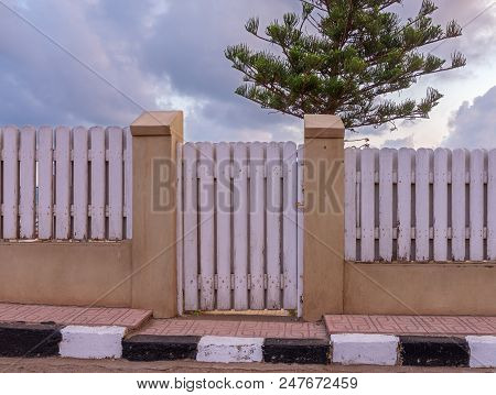 White Weathered Wooden Garden Gate And Fence With Background Of Single Tree And Cloudy Sky At Montaz