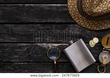 Adventurer Table. Travel Concept. Compass, Loupe, Flask, Hat And Money On Old Wooden Table Backgroun