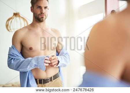 Waist Up Portrait Of Serious Man Gazing In Mirror While Putting On Clothes. He Is Standing And Gathe