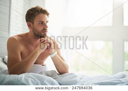 Side View Of Pensive Young Male Sitting On Bed In Morning. He Is Contemplating On Day Plans Before G