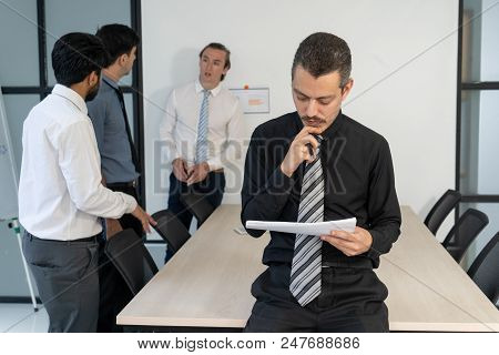 Serious Executive Reviewing Project Documents. Middle Aged Man In Black Shirt And Tie Reading Agreem