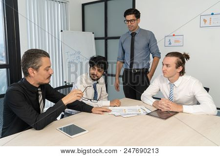 Three Young Managers Reporting To Serious Boss. Four Men In Shirts And Ties Meeting At Conference Ta