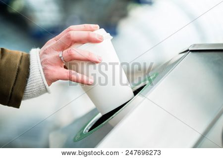Woman using waste separation container throwing away coffee cup made of Styrofoam