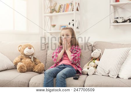 Shocked Little Casual Girl Watching Tv. Frightened Female Kid Sitting On Sofa, Home Alone, Watching