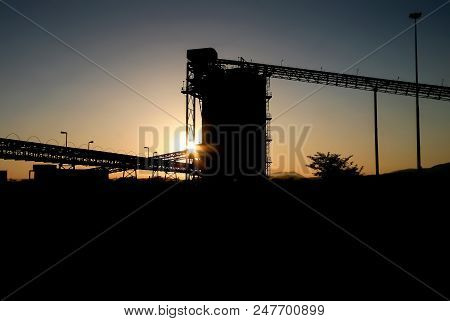 Silhouette of a mining silo and conveyor belts at sunset on a Platinum Mine poster
