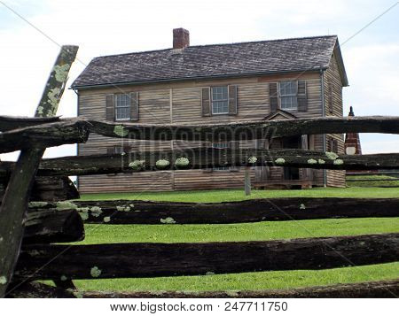 An Old Wooden Home With Log Fence
