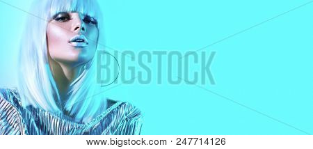 High Fashion model girl in colorful bright neon lights posing in studio, portrait of beautiful woman, trendy glowing metallic make-up. White hair, silver colorful make up.  Cosmic Vivid neon makeup