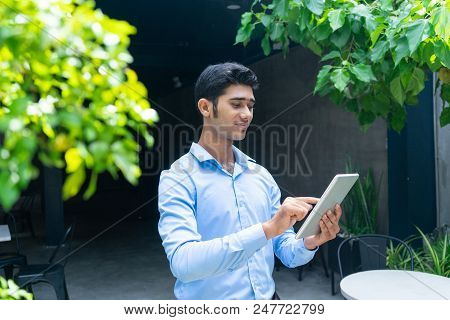 Portrait Of Smiling Young Businessman Using Digital Tablet. Indian Man Networking On Touchpad In Sid
