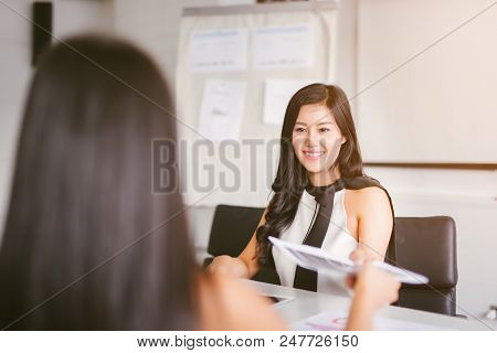 Business woman passing document to manager at the office .The office worker submits a report on the work done to the head. poster