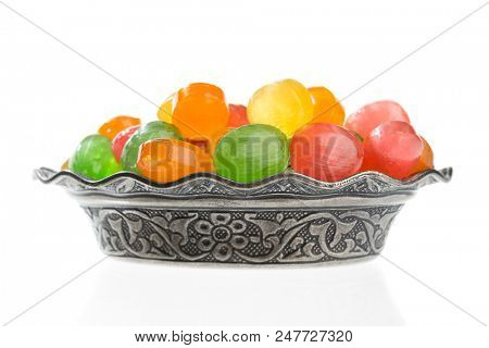 Colorful hard candies in vintage plate isolated on white background.