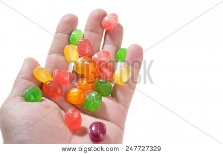 Colorful candies on hand isolated on white background.