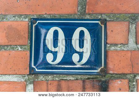 Old Vintage House Address Blue Metal Number 99 Ninety Nine On The Brick Facade Of Residential Buildi
