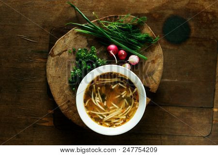 Fresh chicken soup on wooden table, top view
