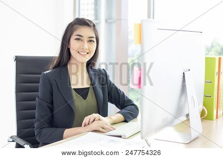Asian Woman Using Computer For Work With Attractive Smiling. Woman Working Concept