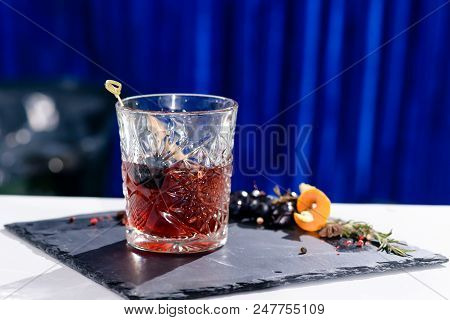 Classic Alcoholic Godfather Cocktail In Rocks Glass On Blue Background, Shallow Dof