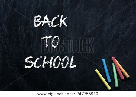 Colored Chalk With Back To School Written In Chalk With A Green Chalkboard Background