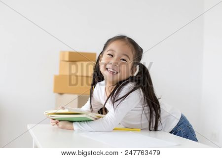 Attractive Little Girl Holding Book With Smiling. Happy Children Lifestyle, Education Concept.