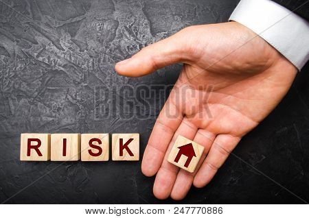 The Realtor's Hand Stretches A Cube With A House Pattern To The Word Risk. The Concept Of Risk, Loss