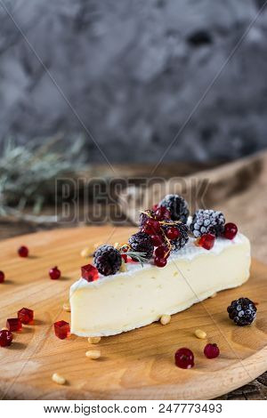French cheese brie, camambert with honey, marmalade and pine nuts on wooden cheese board. Berries marmalade and honey in motion with honey dipper poster