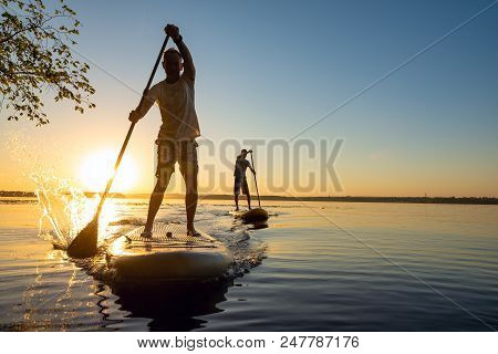 Men, Friends Sail On A Sup Boards In A Rays Of Rising Sun. Stand Up Paddle Boarding - Awesome Active