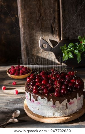 Chocolate Cake With Whipped Cream On Wooden Desk And Wooden Background. Cherry Cake With Chocolate.