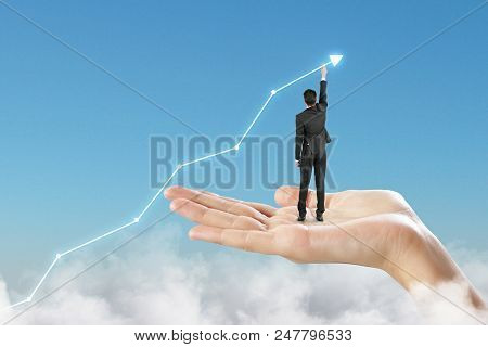 Concept Of Career Growth And Career Planning With Businessman Draws Graph Of Growth Standing At Palm