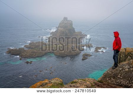 Lonely Tourist Dressed In Waterproof Jacket Standing On The Top Of A Cliff And Admiring The Rocky Fo