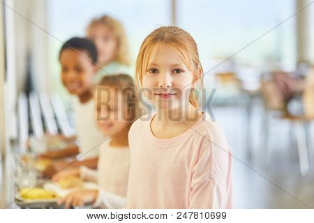 Girls and other children at the buffet in the primary school cafeteria