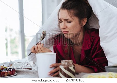 Stressed Woman. Stressed Crying Woman Hiding Under Coverlet While Eating Ice Cream And Other Dessert