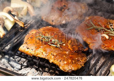 meat with  herbs grilling on barbecue