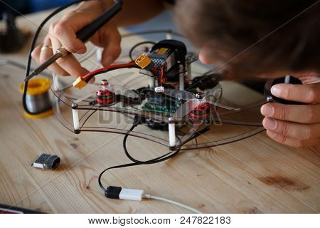 Image of young man with soldering iron chipping mechanism
