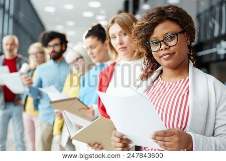 Row of applicants with their resumes preparing for interview with employer