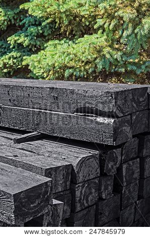 Set Of New Creosote Impregnated Wooden Sleepers Are Stacked On Each Other Against The Background Of