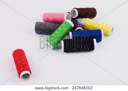 One red bobbin of thread near heap of bobbins of new colorful threads on white background poster