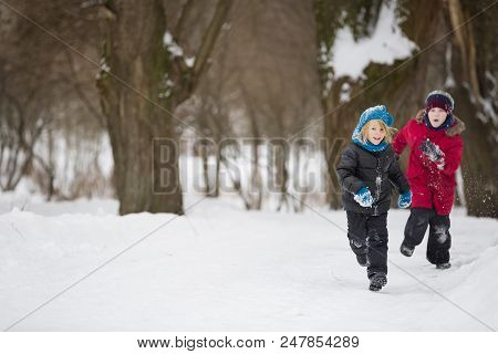 Portrait Of Adorable Little Kid Boys Running On Snow And Playing With Snow Outdoors In The Park. Chi