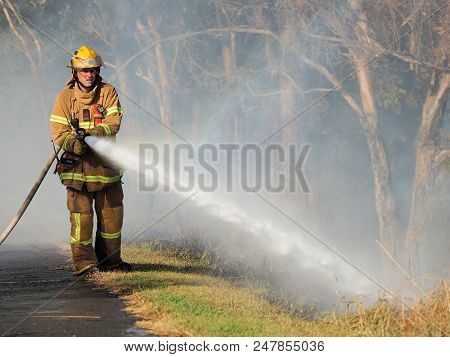 Melbourne, Australia - April 13, 2018: Fire Fighter With A Hose At A Bush Fire In An Suburban Area O
