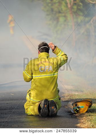 Melbourne, Australia - April 13, 2018: Exhausted Fire Fighter At A Bush Fire In An Suburban Area Of