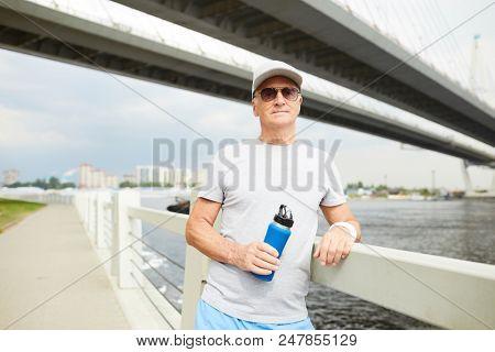 Mature sportsman in activewear leaning on railings of urban bridge by riverside during refreshment break poster