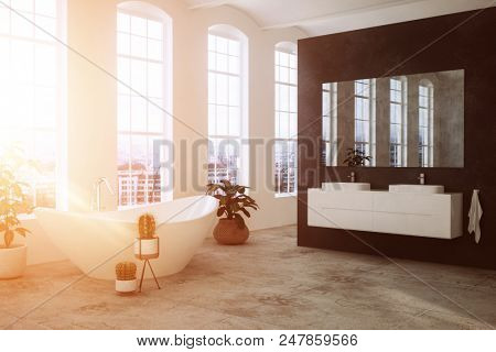 Modern bathroom lit by the warm glow of the sun through large view windows with a freestanding oval tub, double vanity on a black feature wall and plants. 3d rendering