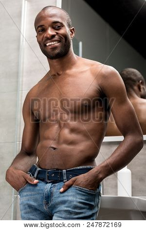 Low Angle View Of Handsome Shirtless African American Man Standing With Hands In Pockets And Smiling