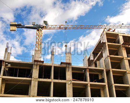 Construction Crane Near Building Under Construction Against Blue Sky. Construction Site.