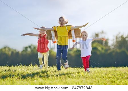 Little children playing astronaut. Girls fleeing and having fun in the park on sunset background. Kid in an astronaut costume dreaming of becoming a spaceman. Family games outdoors.