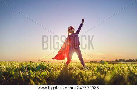 Little child is playing superhero. Kid on the background of sunset sky. Girl power concept