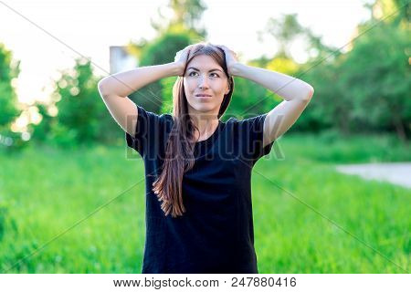 Beautiful Brunette Girl With Long Hair And Black T-shirt. Summer In Nature Among Green Meadows. He H