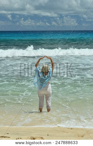 Beautiful Senior Woman Wit Raised Hands Standing On Beach And Looking At Sea